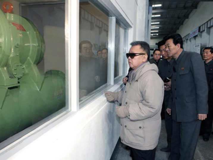Kim Jong Il looking at a machine behind a window
