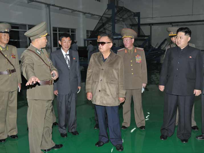 Kim Jong Il looking at a soldiers of the KPA acting as a guide of the production plant