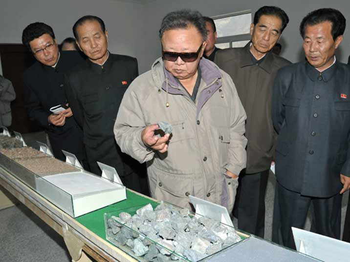 Kim Jong Il looking at iron ore produced from a North Korean state mine