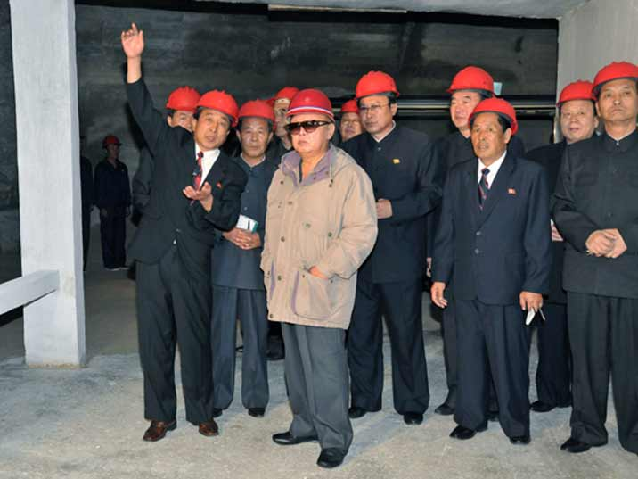 Kim Jong Il looking at a factory while wearing a hard head