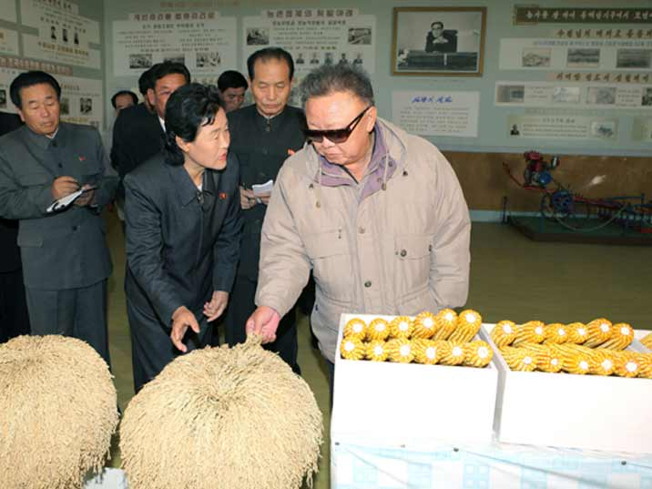 Kim Jong Il looking at corn while being showed around by a lady who woks on the farm