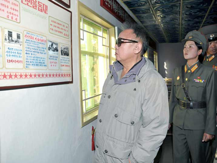 Kim Jong Il looking at board in a small museum of a KPA unit with a female soldier