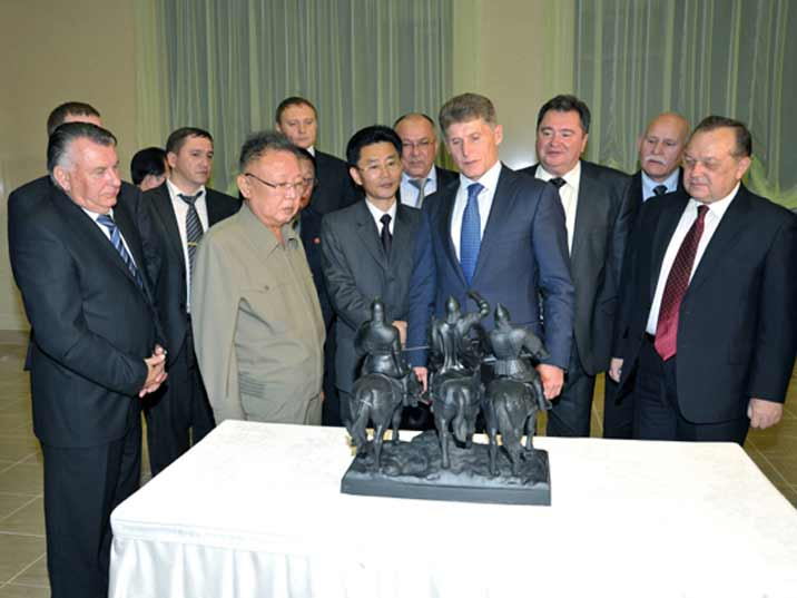 Kim Jong Il looking at a gift from a Russian trade delegation