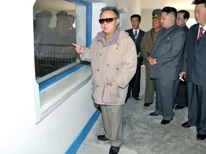 Kim Jong Il looking at stables on a Korean Peoples Army farm in presence of his son Kim Jong Un