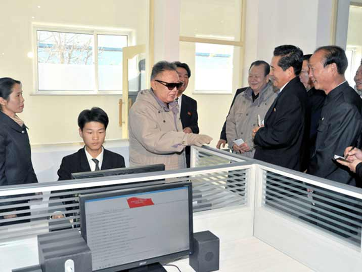 Kim Jong Il looking at the manager of a computer centre while a young man is working on his PC