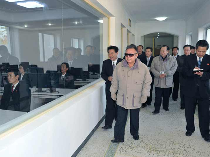 Kim Jong Il looking at a classroom with students following som kind of training