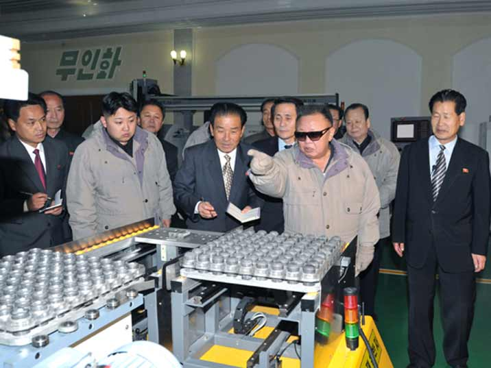 Kim Jong Il looking at machines and giving tips to the factory worker and his son Kin Jung Un