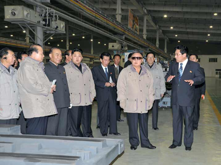 Kim Jong Il looking at the work floor of a factory accompanied by his son Kim Jung Un
