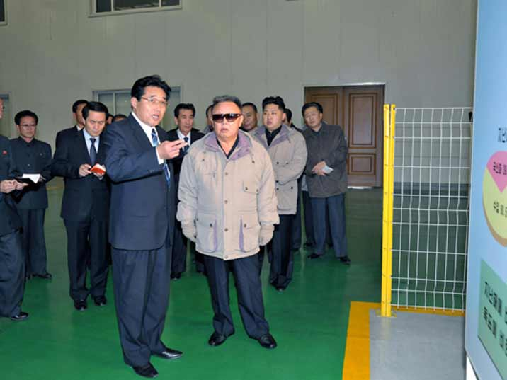 Kim Jong Il looking at statistics about the factory he is visiting