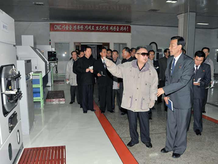 Kim Jong Il looking at a machine in a factory