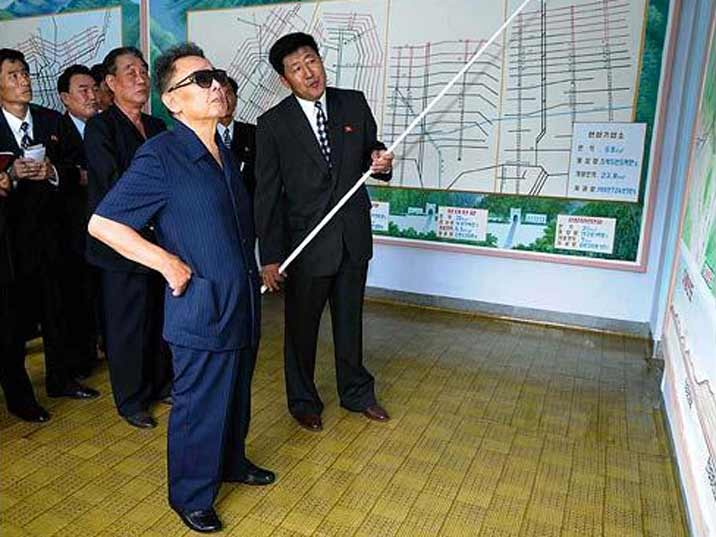 Kim Jong Il looking at a map that shows the mines of the state corporation he is visiting