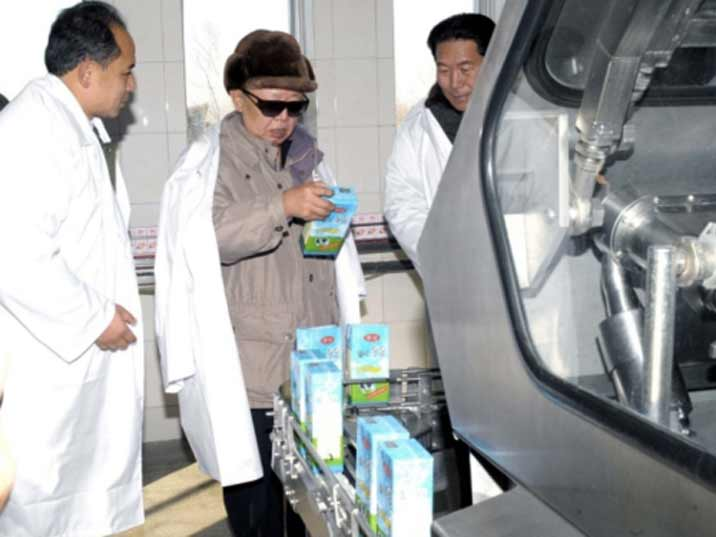 Kim Jong Il looking at a pack of milk produced in a state farm he is visiting