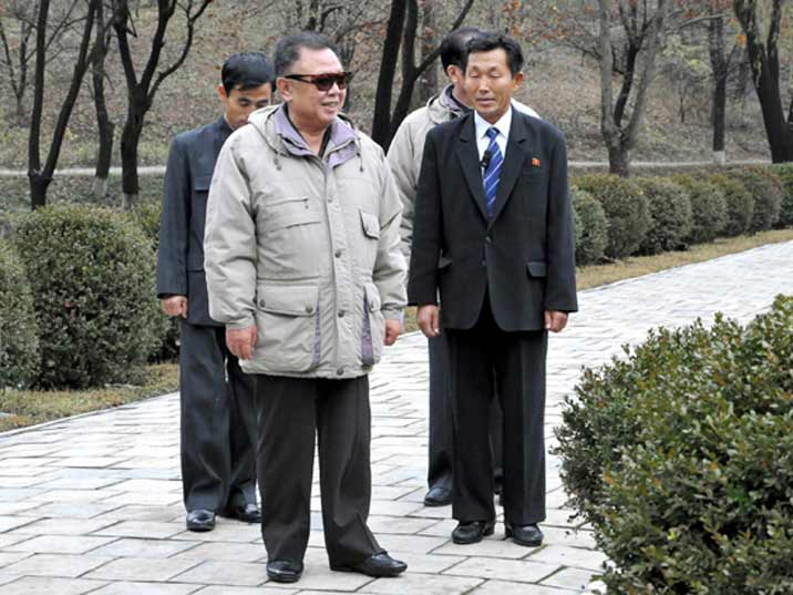 Kim Jong Il looking at bushes while taking a walk during a field guidance visit