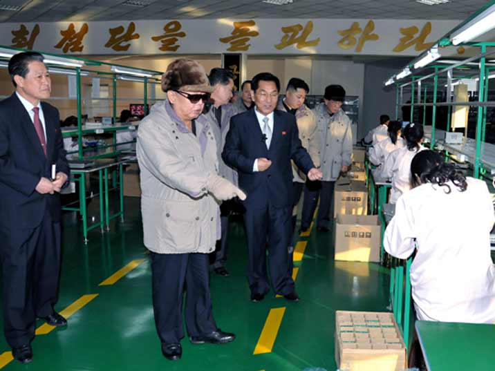 Kim Jong Il looking at workers packaging products in a production facility