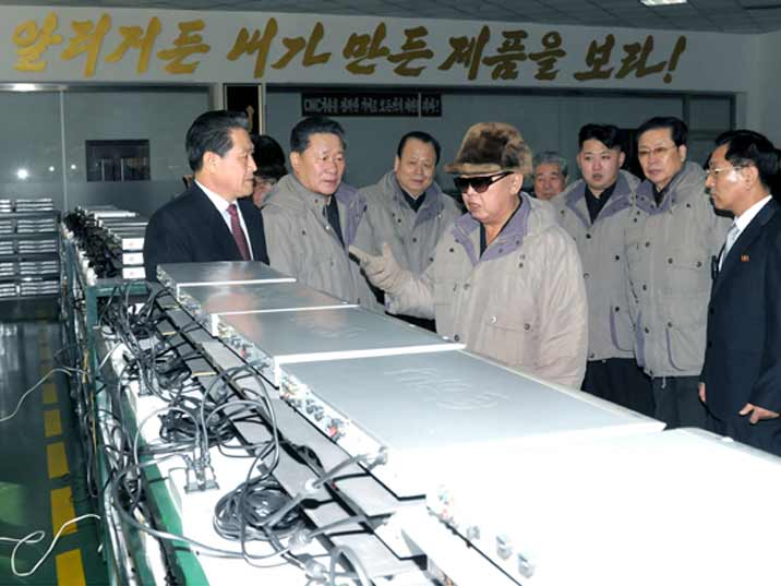 Kim Jong Il looking at DVD player produced in a North Korean high tech factory