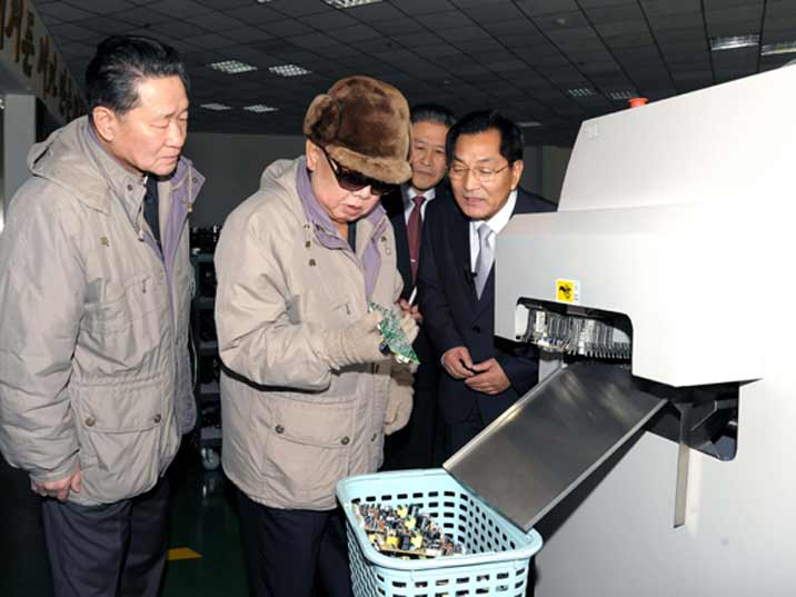 Kim Jong Il looking at part of a DVD player produced in a high tech plant