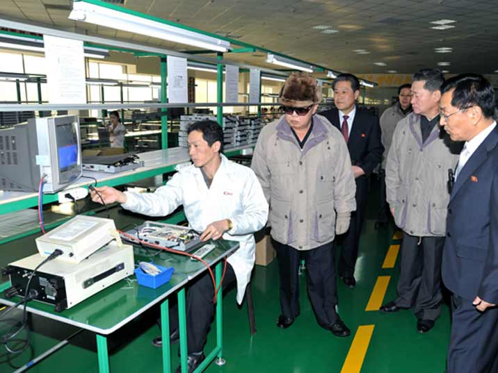 Kim Jong Il looking at worker assembling a DVD player