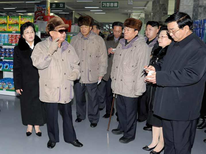 Kim Jong Il looking at the store manager while he gives tips improving customer service
