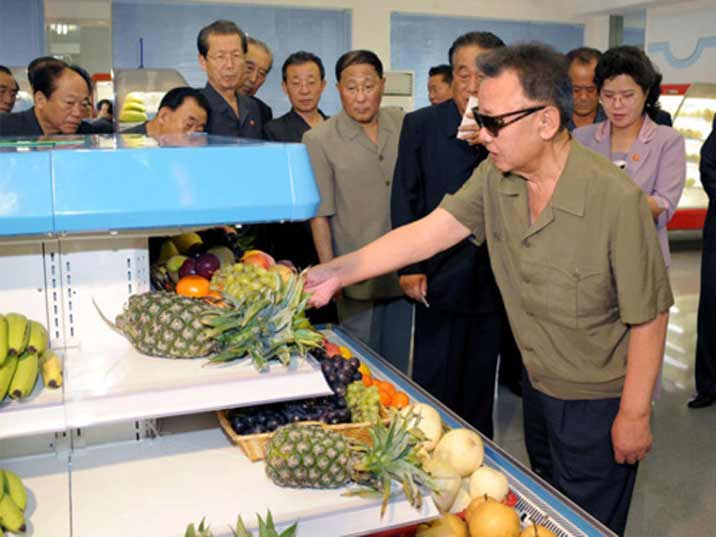 Kim Jong Il looking at fruits including pineapple, grapes, bananas and melons is a Pyongyang store