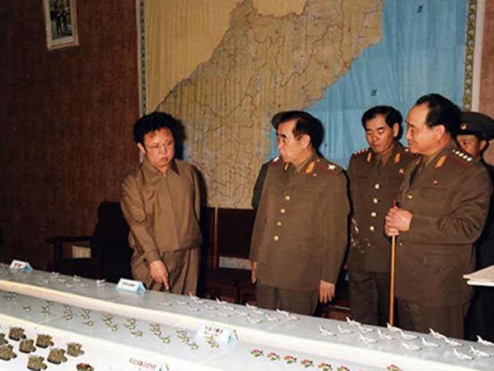 Kim Jong Il looking at aircraft models behind a map of the DPRK with his generals