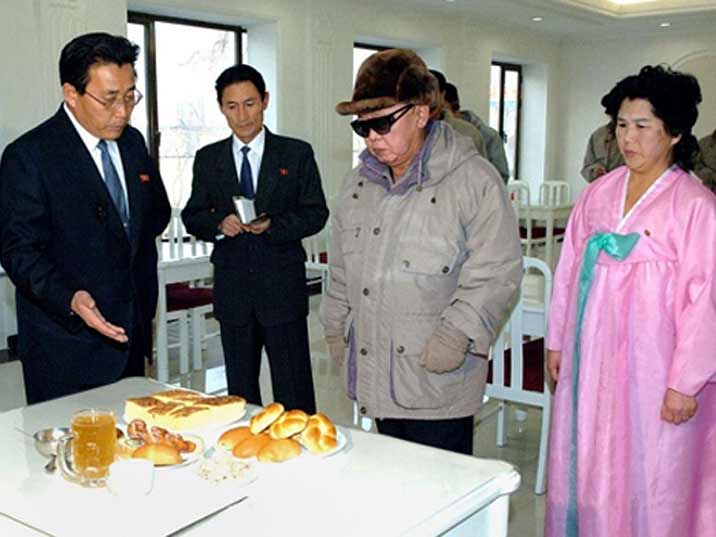 Kim Jong Il looking at cakes in a restaurant