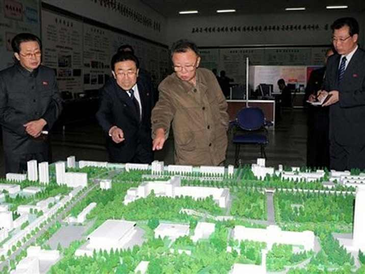 Kim Jong Il looking at a scale model of a city with plenty of green