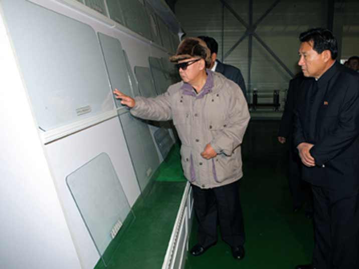 Kim Jong Il looking at glass produced in a factory where he is giving field guidance