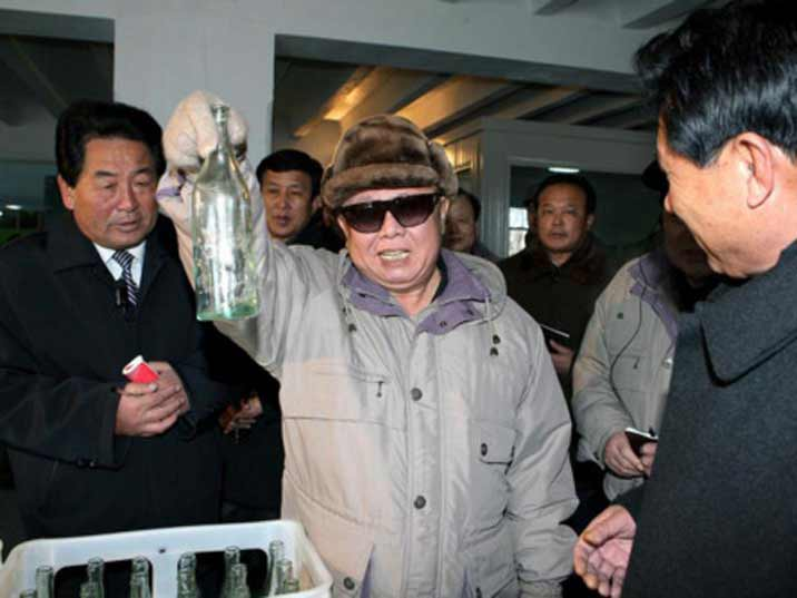Kim Jong Il looking at an empty bottle produced in the factory he is helping to increase productivity