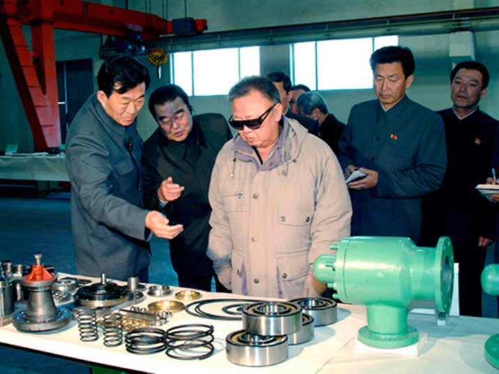 Kim Jong Il looking at parts that can be used in a piping system