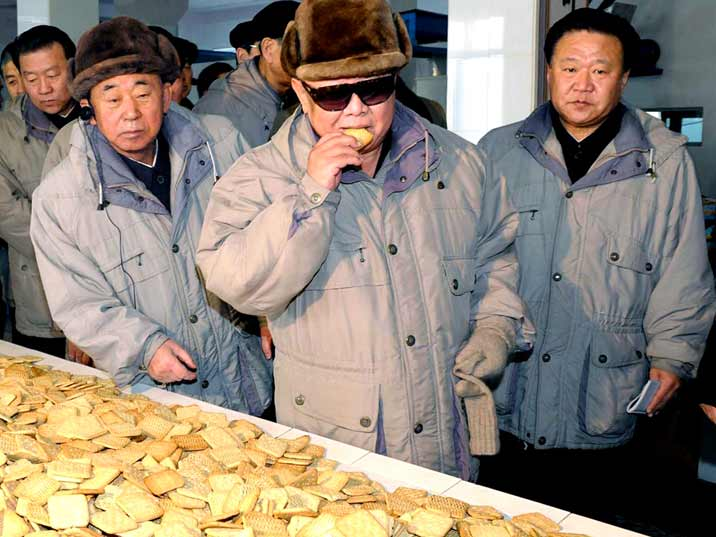 Kim Jong Il eating a cookie while entourage watches him