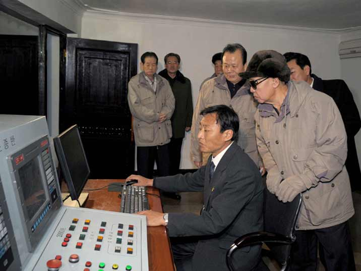 Kim Jong Il looking at a worker operating a machine or process with a computer