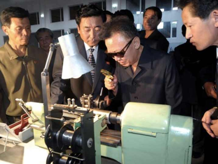 Kim Jong Il looking at something small with a looking glass
