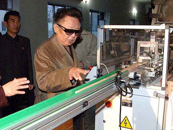 Kim Jong Il looking at a machine in a high tech production facility