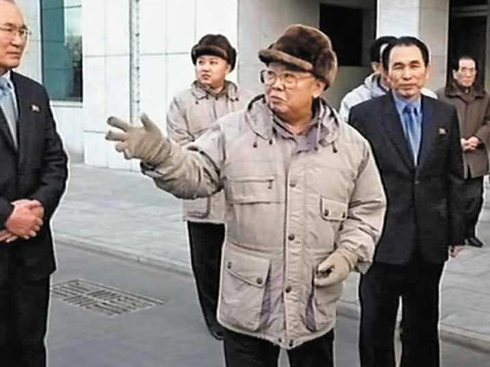 Kim Jong Il looking at people while his son Kin Jung Un stands in the background