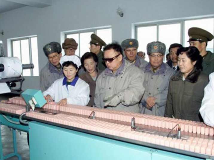 Kim Jong Il looking at soap rolling of a production belt