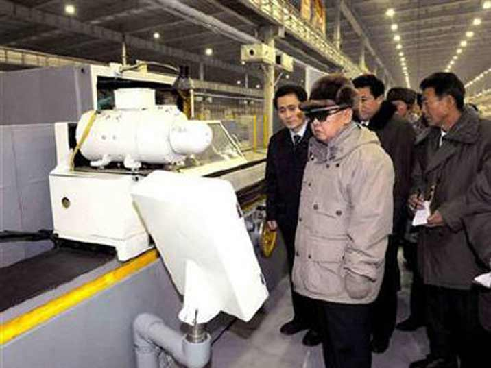 Kim Jong Il looking at a monitor of a production system while he is giving field guidance
