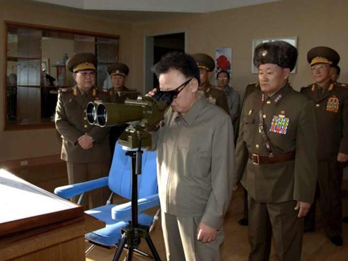 Kim Jong Il looking at a military exercise trough a set of binoculars