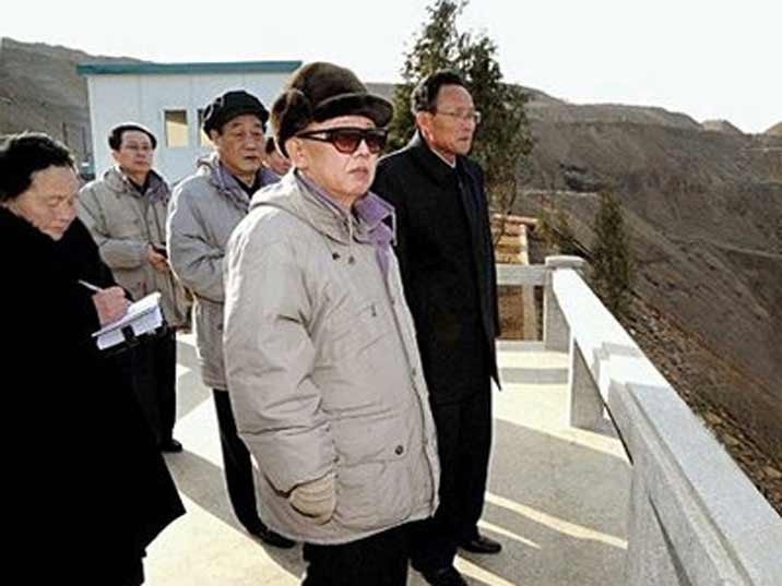 Kim Jong Il looking at fields in a hilly area