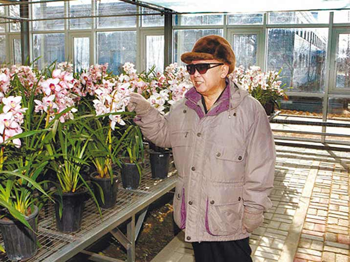 Kim Jong Il looking at flowers produced in a greenhouse