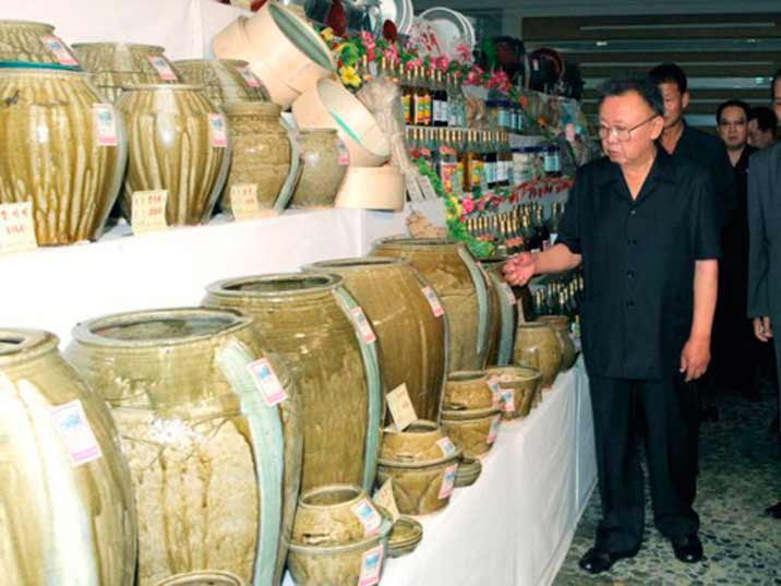 Kim Jong Il looking at pots in various sizes sold in a North Korean warehouse