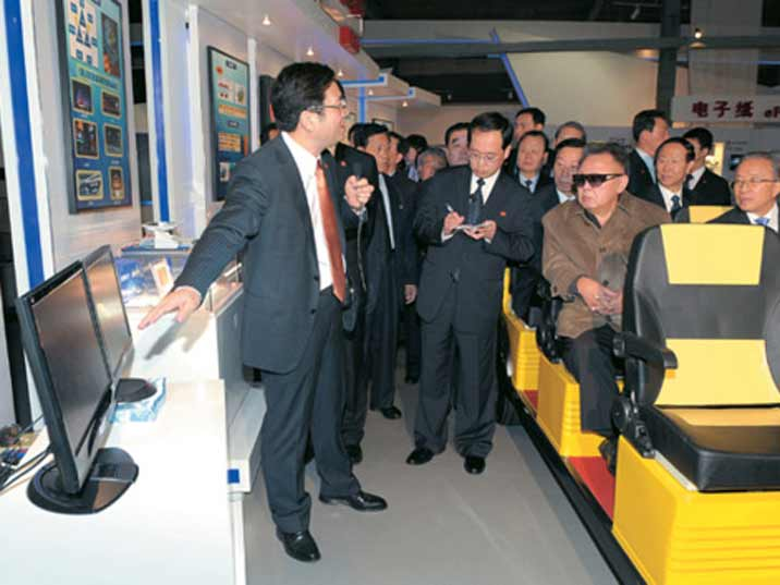 Kim Jong Il looking at a flat screen TV while driven around on an electric train, most likely in China