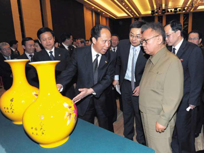 Kim Jong Il looking at a yellow vase that he received as a gift