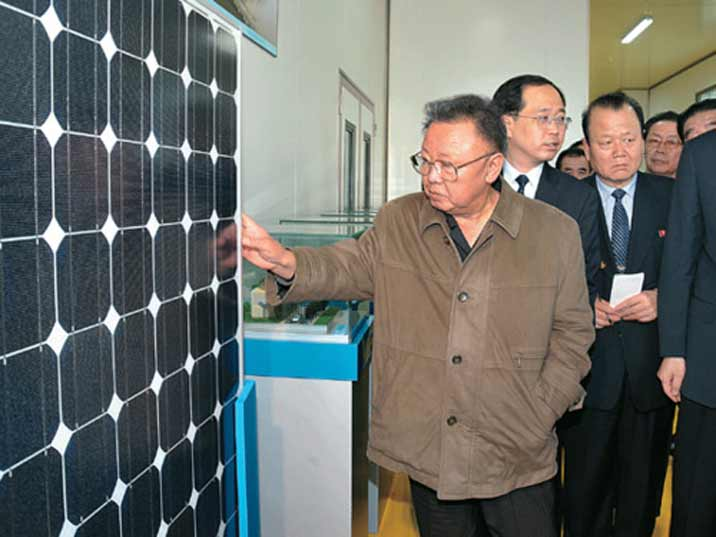 Kim Jong Il looking at solar panels in a high tech production facility