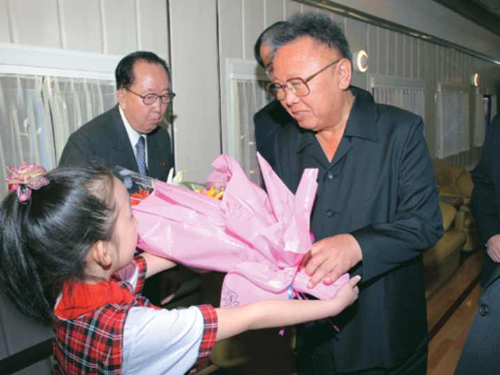 Kim Jong Il looking at a kid who gives him some flowers