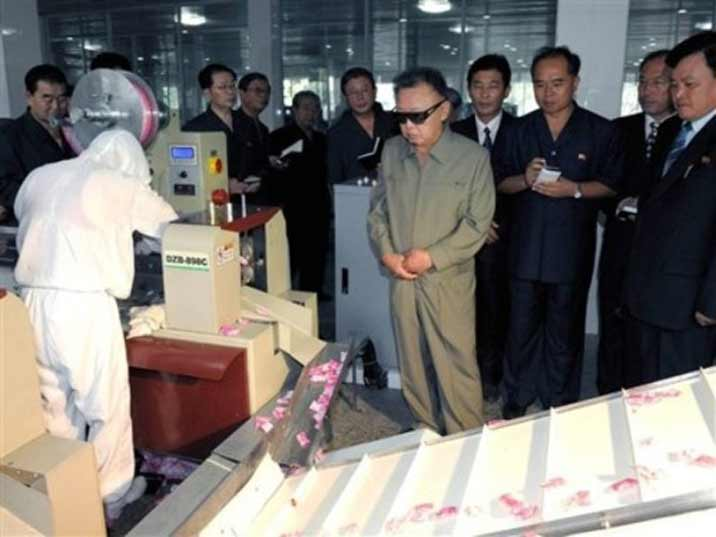 Kim Jong Il looking at an assembly line in a production facility where he is giving field guidance