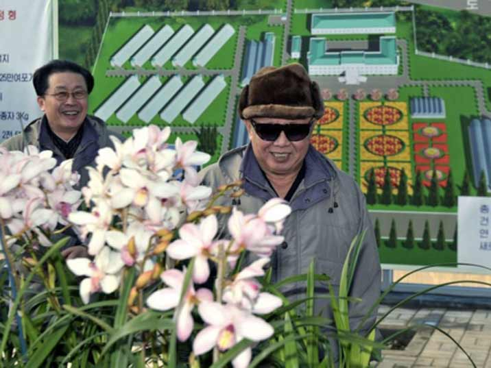Kim Jong Il looking at flowers while visiting a modern plant