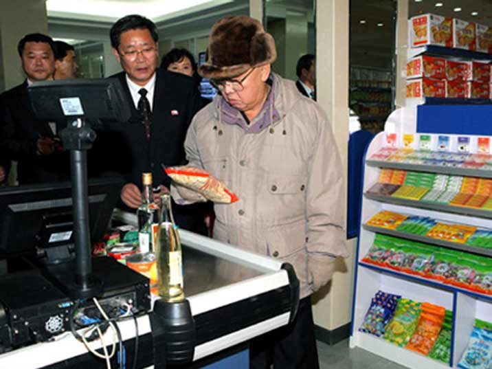 Kim Jong Il looking at candy or an other product at the cash register of a supermarket