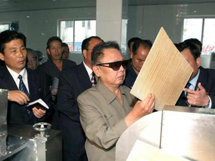 Kim Jong Il looking at pastry used in a cookie bakery