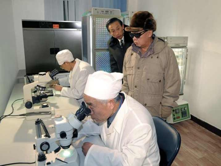 Kim Jong Il looking at a laboratory with scientists looking in a microscope