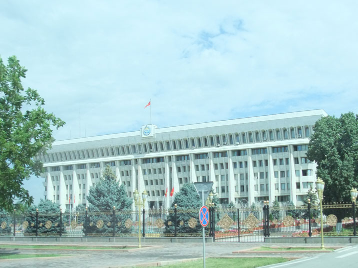 Little girl waling in front of the Kyrgyz parliament building behind the former Lenin Museum